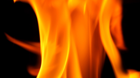 Fire blazing while cooking on black color background and close-up shot.