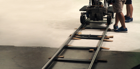 Behind the scenes of production team setting dolly track for camera equipment and video shooting in a big studio.