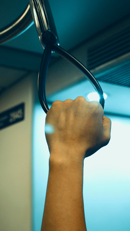 grabing: Big black color train handle and hand grabing for safety and travel by public transportation.
