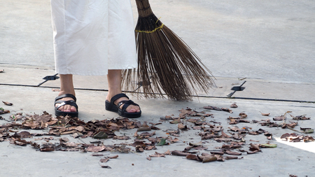 Old woman is sweeping dry leaf on the outdoor cement floor by big long broom.
