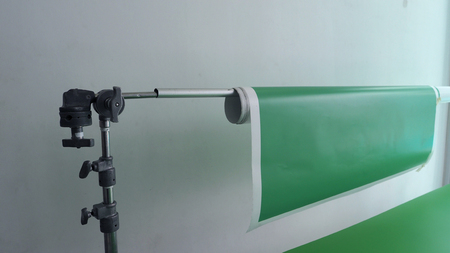 Green screen paper backdrop card board and tripod in home studio for chroma key video production. Stock Photo