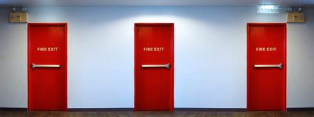 Nooduitgang deur rode kleur metalen materiaal voor veiligheid en houten vloer en witte muur binnen gebouw. Stockfoto