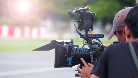 Image floue de tournage de film ou de production vidéo et équipe de tournage avec équipement de caméra à l'extérieur et effet de lumière.