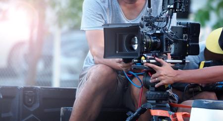 Imagem embaçada de filmagem ou produção de vídeo e equipe de equipe de filmagem com equipamentos de câmera em local ao ar livre e efeito de luz flare.
