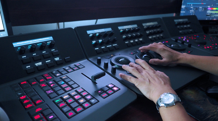 Telecine controller machine and man hand editing or adjusting color on digital video movie or film in the post production stage. Stock Photo - 90471322