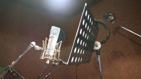 Microphone with shockmount and pop filter on tripod and note stand in recording sound studio video production.