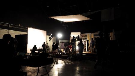 derrière les scènes de l & # 39 ; équipe de l & # 39 ; équipe de la machine à sous et un appareil photo vidéo silhouette en studio.