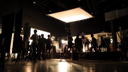 Za kulisami filmowania sylwetka ekipy produkcyjnej i sprzęt fotograficzny w studio.