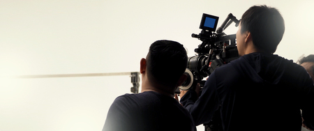 Behind the scenes of video camera shooting by film crew team production people in big studio for commercial works.
