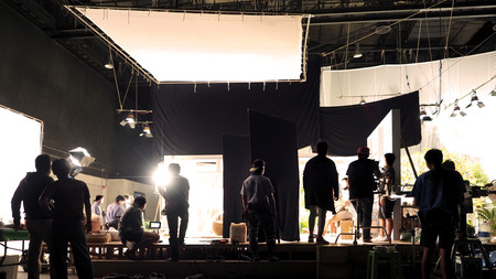 Silueta de personas que trabajan en un gran estudio de producción para filmar o grabar videos de películas con cámara digital y conjunto de iluminación. Foto de archivo