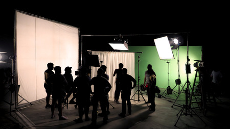 Behind the scenes of TV commercial movie film or video shooting production which crew team and camera man setting up green screen for chroma key technique in big studio. Фото со стока