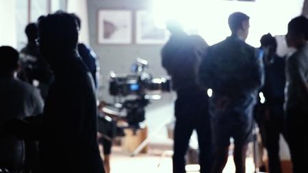 Rozmyte obrazy sylwetki ludzi ekipy filmowej pracującej za kulisami przy kręceniu produkcji wideo z profesjonalnym sprzętem, kamerą i oświetleniem w studio. Zdjęcie Seryjne