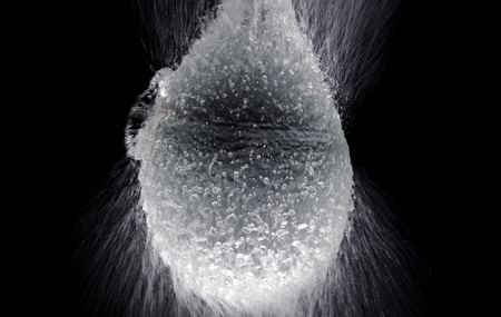 Water balloon exploding or splashing which represent power of refreshing or freshness for viewer and blasted by pencil in hand on black background in the studio.