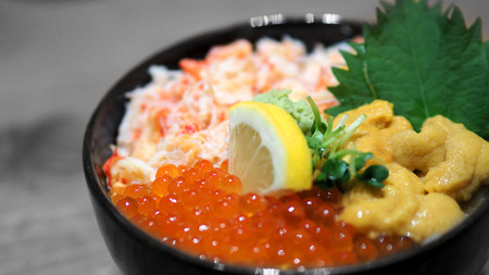 Close-up images of japanese seafood rice bowl or kaisendon sashimi donburi which have fresh ogura, uni, giant crab and topping with lemon on rice in the black bowl on the wood table from top view angle camera.