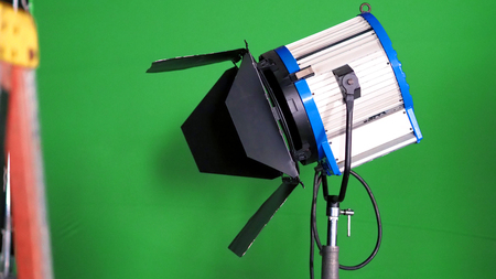 Big studio LED spotlight for video movie or photo film production with green screen background for chroma key technique in post lab process and professional equipment such as tripod and others.