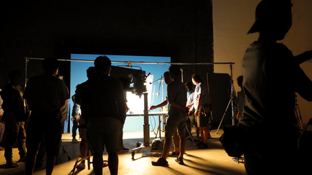 Behind the scenes of video production shooting studio in silhouette which have professional equipment such as camera, tripod and blue screen backdrop set for chroma key technique in post process and many film crew team working for TV commercial or online movie 版權商用圖片