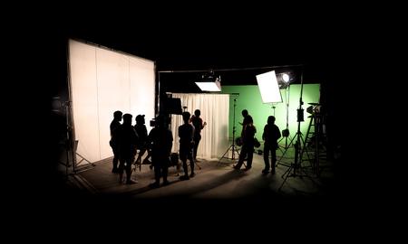 Profili le immagini della produzione video dietro le quinte o b-roll o realizzazione di film commerciali TV che la troupe cinematografica lightman e cameraman lavorano insieme al regista in un grande studio con attrezzature professionali