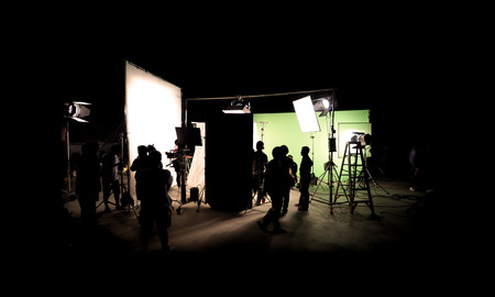 Silhouette images of video production behind the scenes or b-roll or making of TV commercial movie that film crew team lightman and cameraman working together with director in big studio with professional equipments