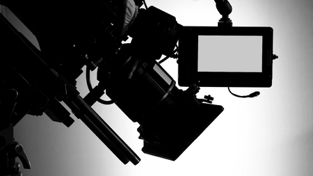 Silhouette images of video camera in tv commercial studio production which operating or shooting by cameraman and film crew team in set and prop on professional crane and tripod for easy to pan tilt or shift