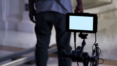 Behind the scenes of film or video production monitor in tv commercial shooting and movie crew team setting up for next shot and waiting for director and agency or clients approve