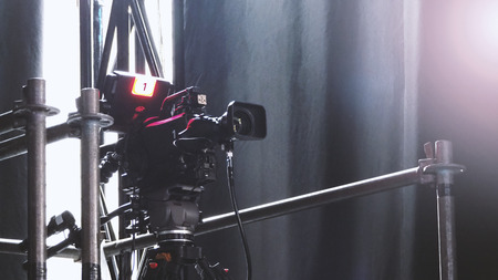 Blurry images of broadcast camera on the crane tripod for easy to shooting or recording and broadcasting content in studio production to on air tv or online internet live show.