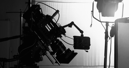 Video camera in film or movie production on tripod and professional gear which shooting in location or studio with crew team and beautiful prop or set and ready to online live broadcast or tv on air l