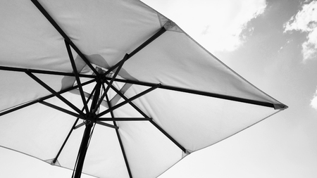 White fabric color texture beach umbrella and brown wood tripod with white cloud and clear blue sky summer sunlight day in low angle view camera for travel asia Thailand Pattaya.