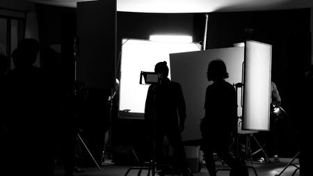 Studio di ripresa dietro le quinte in immagini di silhouette che la troupe cinematografica lavora per le riprese di film o video con illuminazione professionale e attrezzature come fotocamera, treppiede, soft box, monitor