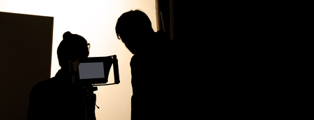 Shooting studio behind the scenes in silhouette images which film crew team working for filming movie or video with professional lighting and equipment such as camera, tripod, soft box, monitor