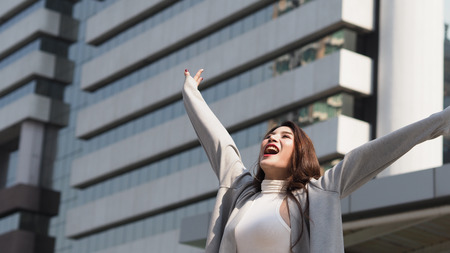 Beautiful asian business woman happy and cheerful or successful feeling with job which action like a winner by raise or lift up arms to the sky and shout yeah at outdoor city in summer season. Stock Photo