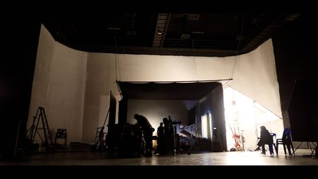 Behind the shooting of video online commercial production and film crew team working and setting light or camera or soft box and equipment set up in big studio in silhouette style Stok Fotoğraf