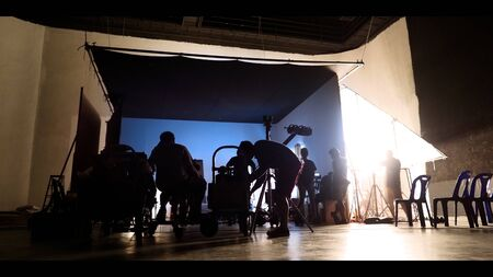 Behind the shooting of video online commercial production and film crew team working and setting light or camera or soft box and equipment set up in big studio in silhouette style 版權商用圖片