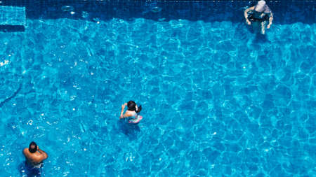 Swimming pool top view angle which blue color clear water and sun light reflect on surface texture and concept images for relaxation or vacation or sport in the tropical summer and for healthy lifestyle