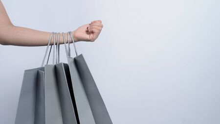 Shopping bag grey color hold on by business asian woman arm and white background which represent shop sale season or online-shopping or e-commerce or clearence sales or shopaholic concept