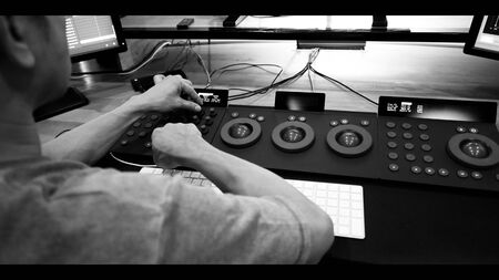 Behind of telecine controller machine and colorist man hand editing or adjusting color on digital video movie or film in the post production stage which very technical in the dark room lab. Stok Fotoğraf