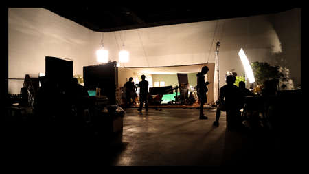 Behind the shooting video production and lighting set for filming which movie crew team working and silhouette shadow of camera and professional equipment in big studio for commercial advertising.