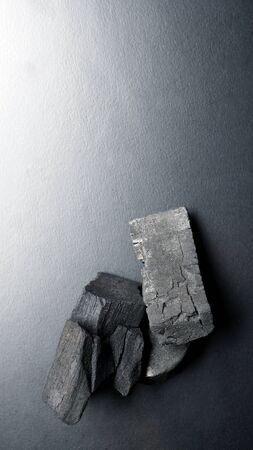 Close-up images of black color charcoal on black background that made from natural wood which represent energy power concept or healthy or use for absorb odor in the room or refrigerator.
