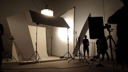 Silhoutte zdjęcia produkcji wideo i zestaw oświetleniowy do kręcenia pracy ekipy filmowej oraz sylwetka cienia kamery i profesjonalnego sprzętu w dużym studiu reklamowym.