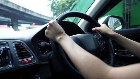 Close-up images of woman hands driving and controling car with confidence and safety which car moving to the Bangkok city Thailand for roadtrip and on the road no traffic jam.