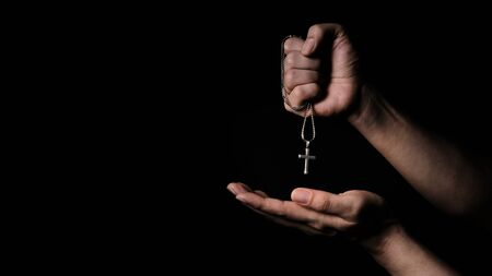 Close-up images of crucifix pendant necklace in man hand on black color background in studio which represent praying for god or jesus and thank gods for giving peaceful and faithful to people