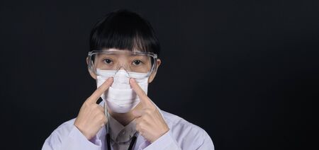 Asian woman doctor wearing or putting medical mask which prevent dangerous coronavirus or covid-19 pandemic virus