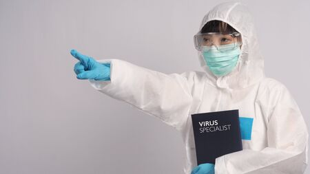 Asian woman doctor in PPE suit with hood and wearing medical mask and gloves for best protection from chemical or virus such as coronavirus or covid-19 and represent virus specialist and white background. 版權商用圖片
