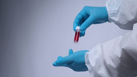 Blood tests in clear tube on doctor hands with blue medical gloves and PPE suit which represent coronavirus or 2019-ncov or covid-19 pandemic screening test that positive results or infected