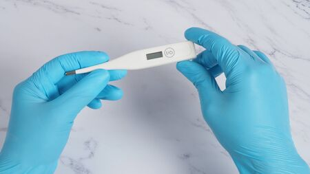 Digital thermometer white color in doctor hands wearing hospital medical gloves light blue color which can shown checking temperature numbers in celsius or fahrenheit degree for pandemic fever