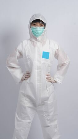 Middle aged asian nurse woman wearing PPE body suit or personal protective equipment which for use in pandemic virus infected situation with medical mask, gloves, goggles