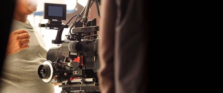 Behind the shooting production crew team and hd video camera and equipment in studio which includes big tripod, soft box light, monitors, lens for making online web film or movie or live broadcasting 版權商用圖片 - 146964170