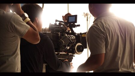 Behind the shooting production crew team and hd video camera and equipment in studio which includes big tripod, soft box light, monitors, lens for making online web film or movie or live broadcasting