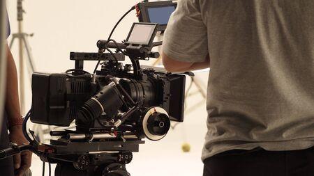 Derrière l'équipe de production de tournage et la caméra vidéo HD et l'équipement en studio qui comprend un grand trépied, une lumière de boîte à lumière, des moniteurs, un objectif pour faire un film ou un film en ligne ou une diffusion en direct