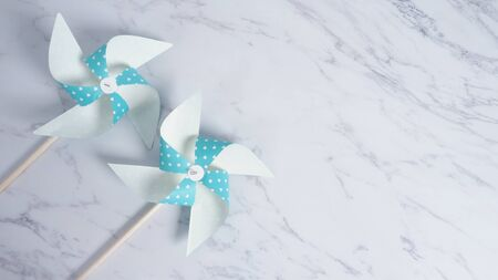 Wind wheel paper real toy on white color marble stone background which made from origami hand made on light blue colour japanese special material and wood stick 版權商用圖片 - 148261953