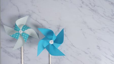 Wind wheel paper real toy on white color marble stone background which made from origami hand made on light blue colour japanese special material and wood stick 版權商用圖片 - 148261961